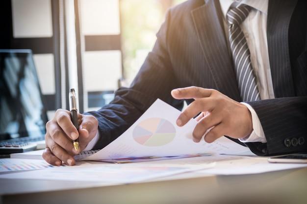 Início do processo de trabalho. empresário que trabalha na mesa de madeira com novo projeto de finanças. caderno moderno na mesa. pen segurando a mão. Foto Premium