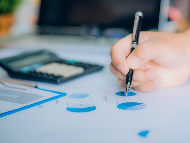 Início do processo de trabalho. empresário trabalhando na mesa de madeira com novo projeto de finanças. caderno moderno na mesa. caneta segurando a mão Foto Premium