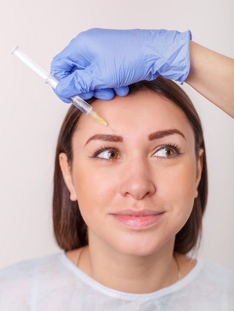 Injeção plástica no rosto feminino bonito Foto Premium