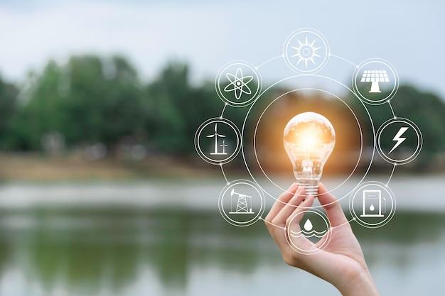 Inovação e conceito de energia da mão segura uma lâmpada Foto Premium