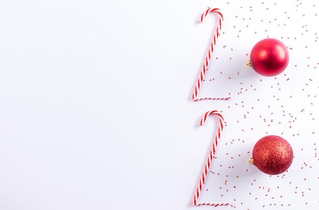 Inscrição 2020 do bastão de doces e bola vermelha em fundo branco. ano novo conceito. Foto Premium