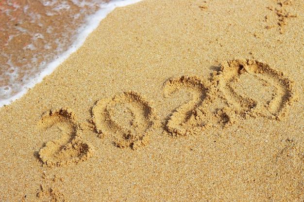 Inscrição 2020 na areia dourada close-up, vista superior Foto Premium