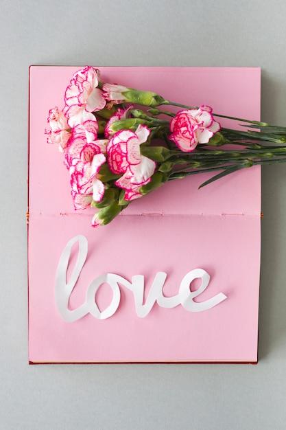 Inscrição de amor branco com flores no caderno Foto gratuita
