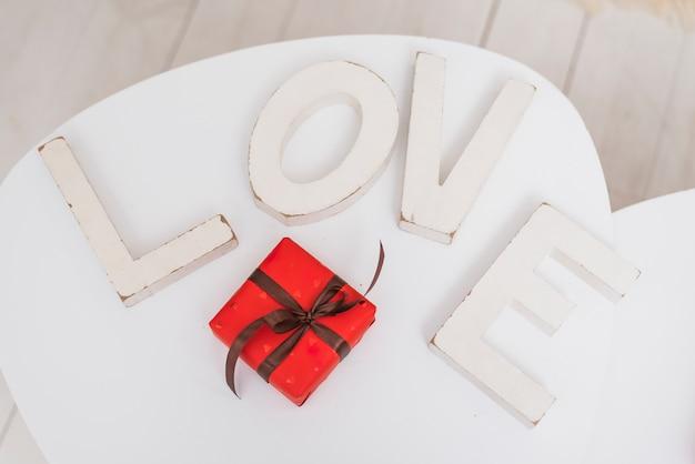 Inscrição de amor branco grande perto de caixa de presente vermelha Foto gratuita