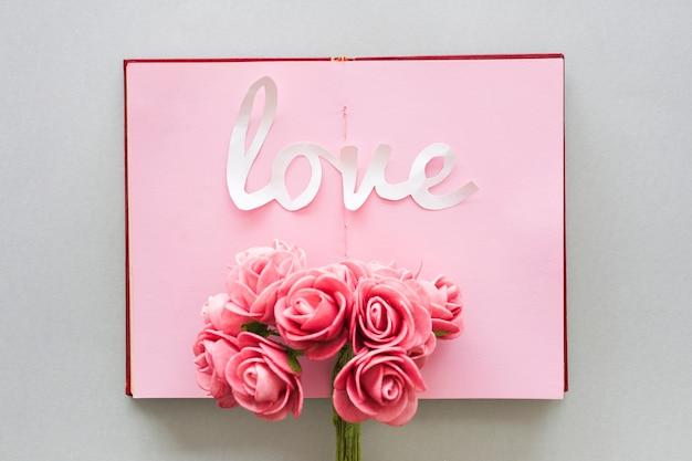 Inscrição de amor com buquê de rosas no notebook Foto gratuita