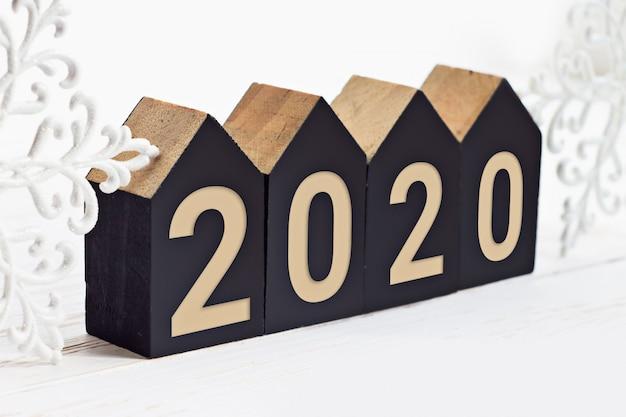Inscrição de ano novo 2020 em cubos de madeira em forma de uma casa em um fundo branco de madeira Foto Premium