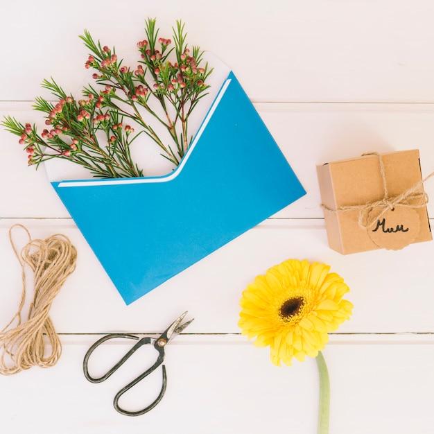 Inscrição de mãe com presente, gerbera e envelope Foto gratuita