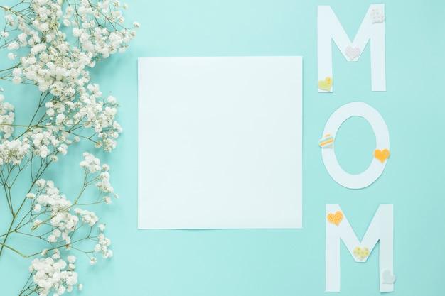 Inscrição de mãe com ramos de flores e folha de papel Foto gratuita