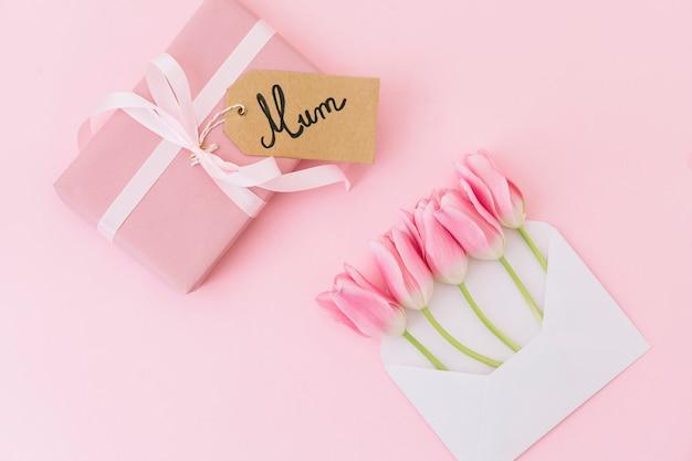 Inscrição de mãe com tulipas em envelope e caixa de presente Foto gratuita