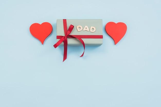 Inscrição de pai com caixa de presente e corações na mesa Foto gratuita