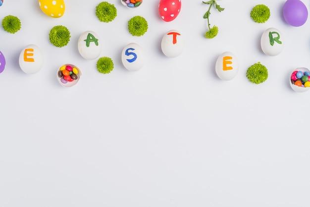 Inscrição de páscoa em ovos com flores na mesa Foto gratuita