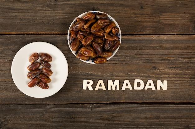 Inscrição de ramadã com fruta de datas na mesa Foto gratuita