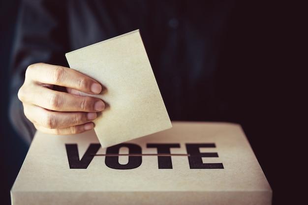 Inserção de papel marrom na caixa de votação, conceito de democracia, tom retrô Foto Premium