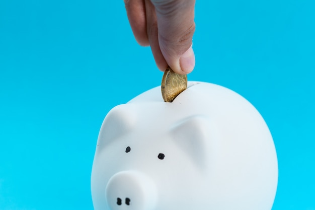 Inserir uma moeda em um cofrinho Foto Premium