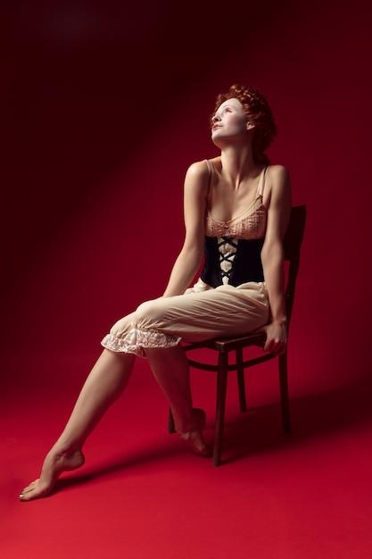 Insônia à noite de verão. jovem ruiva medieval como uma duquesa em espartilho preto e roupa de noite, sentada na cadeira na parede vermelha. conceito de comparação de eras, modernidade e renascimento. Foto gratuita