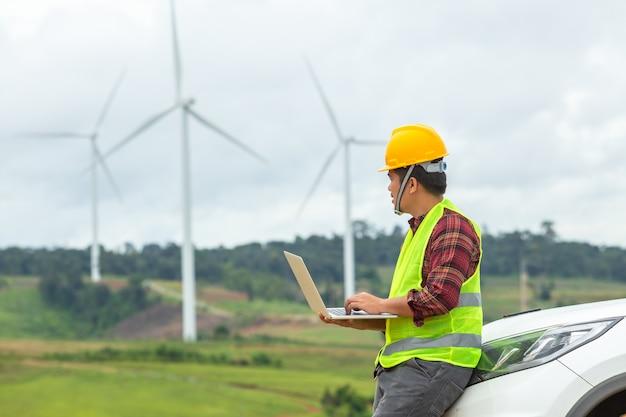 Inspeção do coordenador do moinho de vento e turbina eólica da verificação de progresso no canteiro de obras usando um carro como um veículo. Foto Premium