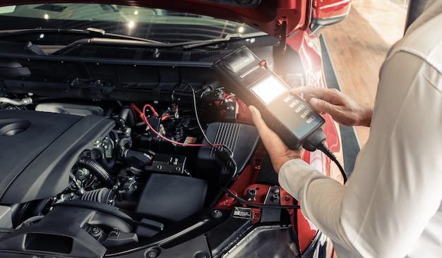 Inspeção do homem segurando a bateria capacidade tester voltímetro. para manutenção de serviço de reparação industrial para motor. na imagem de automóvel automóvel de transporte de fábrica Foto Premium