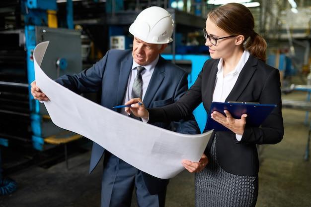 Inspetor sênior revisando os planos da fábrica Foto Premium