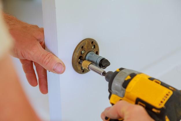 Instalação de bloqueio de carpinteiro com furadeira elétrica na porta de madeira interior Foto Premium