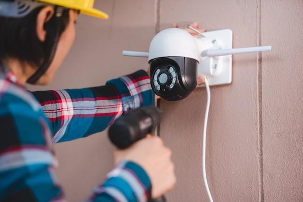 Instalação de cftv com jovens técnicos asiáticos. instalação como câmera ip wifi conceito: câmera ip sem fio Foto Premium