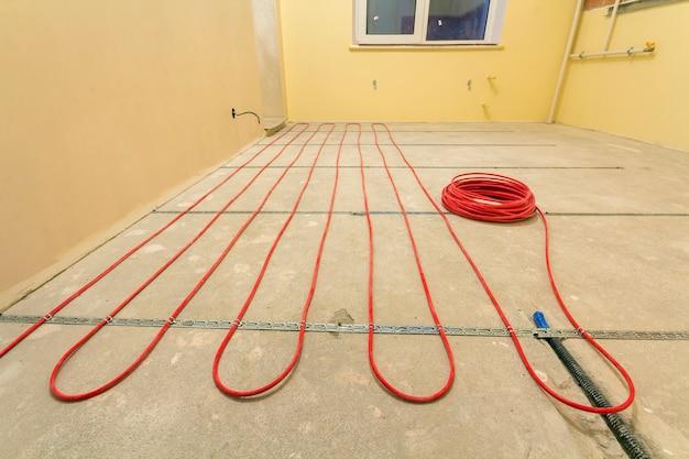 Instalação de fio de cabo elétrico vermelho no piso de cimento na pequena sala inacabada com paredes de gesso. renovação e construção, conceito confortável casa quente. Foto Premium
