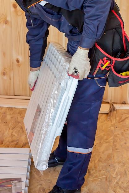 Instalação do radiador de aquecimento. construção de casas e apartamentos. construtor. Foto Premium
