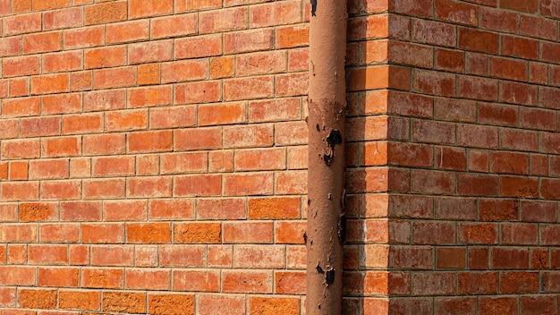 Instalação do sistema de tubulação de água na parede de tijolos laranja Foto Premium