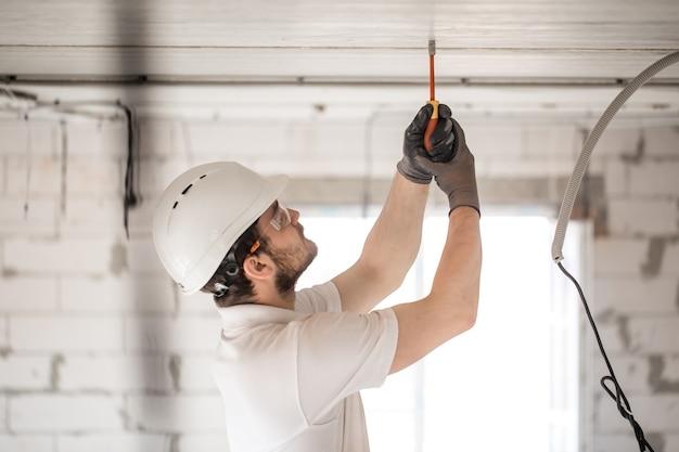 Instalador de eletricista com uma ferramenta nas mãos, trabalhando com cabo no canteiro de obras. Foto gratuita