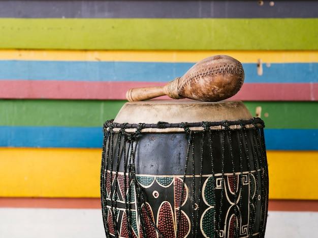 Instrumentos de percussão ao lado da parede de listras multicoloridas com espaço para texto Foto gratuita
