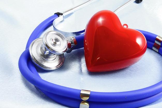 Instrumentos médicos, estetoscópio e close up vermelho do coração. Foto Premium