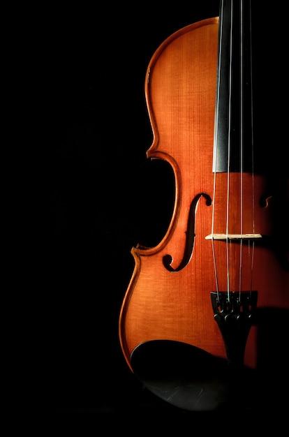 Instrumentos musicais de orquestra de violino closeup em fundo preto Foto Premium