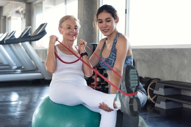 Instrutor com mulher sênior, esticando o exercício no ginásio. estilo de vida saudável idoso e conceito de treino. Foto Premium