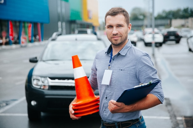 Instrutor de direção coletando cones de plástico Foto Premium