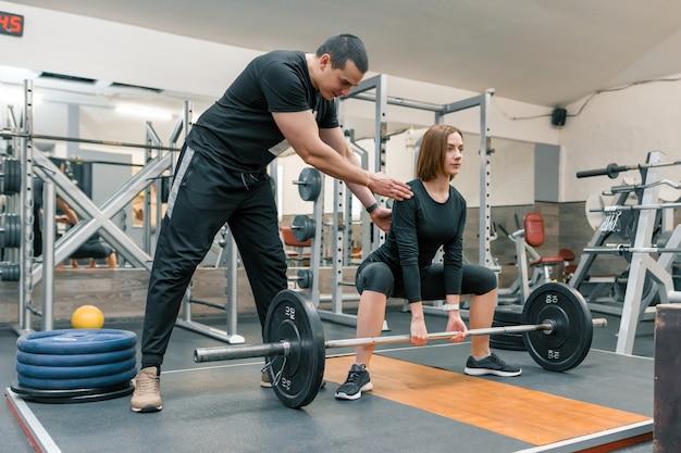 Instrutor de fitness pessoal masculino, ajudando a jovem a fazer exercícios Foto Premium