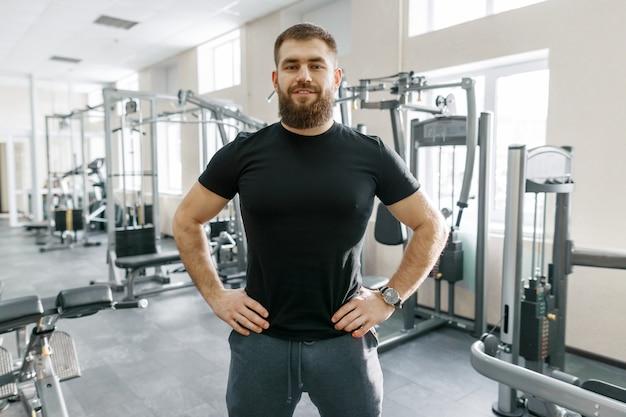 Instrutor de fitness pessoal no ginásio, olhando para a câmera Foto Premium