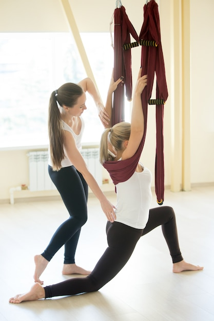 Instrutor de ioga aérea ajudando a mulher a fazer pose de lunge baixo Foto gratuita