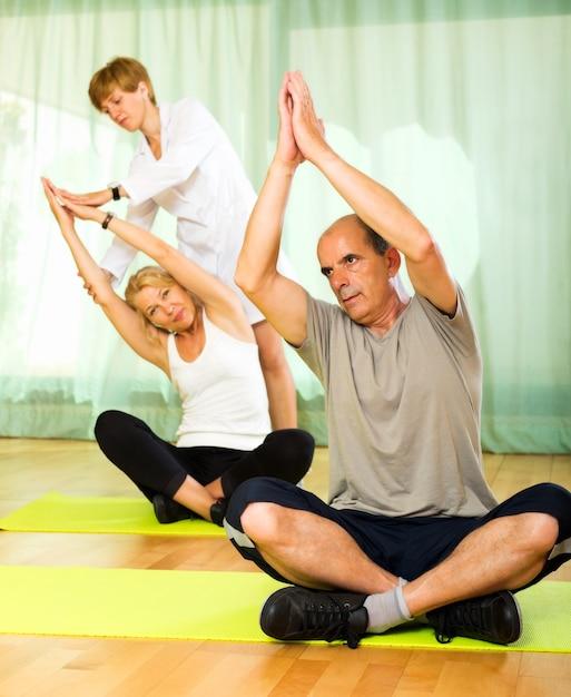 Instrutor de ioga que mostra asana para um casal maduro Foto gratuita