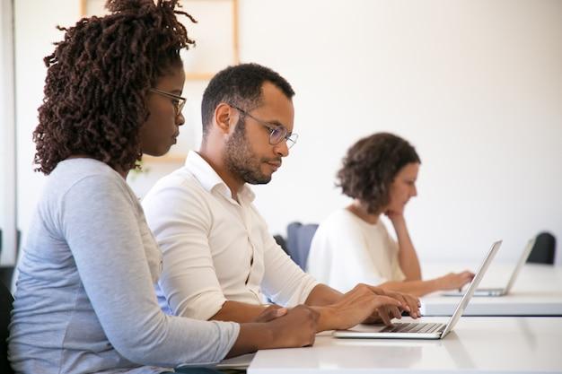 Instrutor e estagiário usando o computador juntos Foto gratuita
