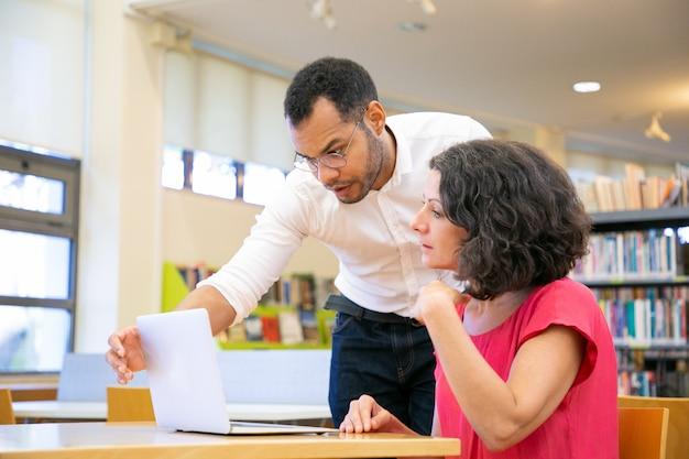 Instrutor que verifica o trabalho do estudante na biblioteca Foto gratuita