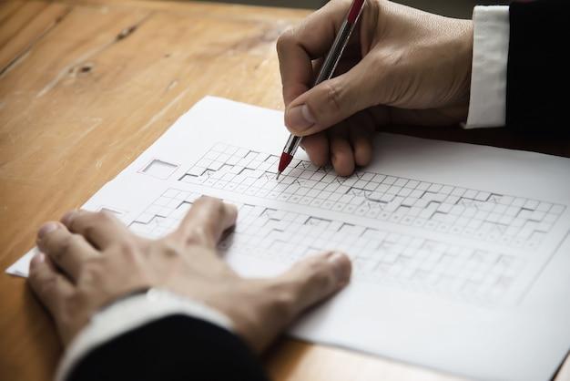 Instrutor verificando o exame de folha de respostas de escolhas múltiplas - pessoas de educação que trabalham com o conceito de teste de papel Foto gratuita
