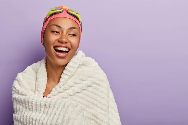 Instrutora de natação esportiva ri feliz, enrolada em toalha branca, dá aula para trainee, tem dentes perfeitos, pele saudável, estilo de vida ativo, exercícios em piscina coberta. menina nadadora com óculos de proteção Foto gratuita