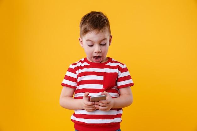 Inteligente menino animado lendo a mensagem no celular Foto gratuita