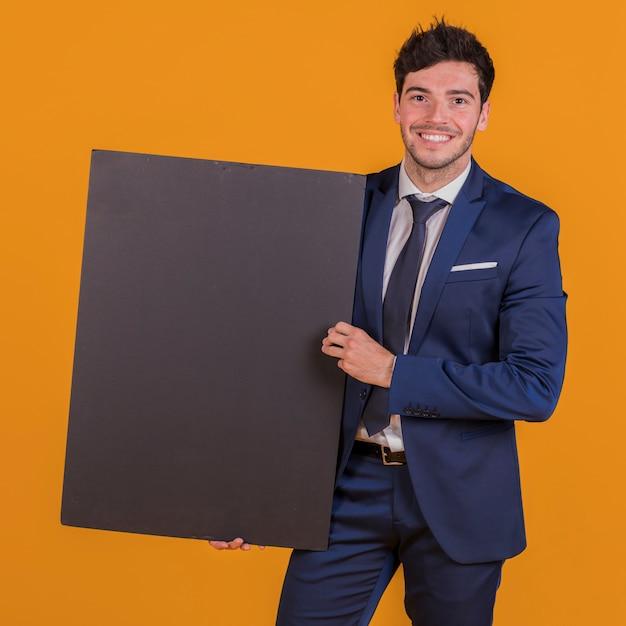 Inteligente sorridente jovem segurando o cartaz preto na mão contra um pano de fundo laranja Foto gratuita