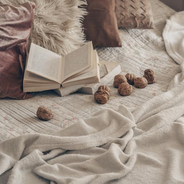 Interior aconchegante da sala de estar com um livro aberto com nozes. leia, descanse. conceito de fim de semana de inverno. conceito aconchegante de outono ou inverno. Foto Premium