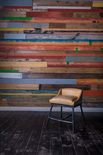 Interior com multi colorido parede de madeira escura piso de madeira e vintage pequena cadeira Foto Premium