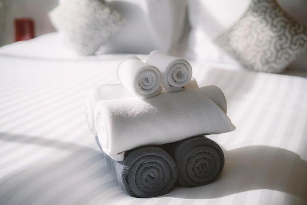 Interior da casa com rolo de toalhas brancas na cama no quarto Foto Premium