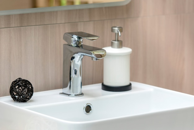 Interior da moderna casa de banho com pia branca e torneira, pia close-up Foto Premium