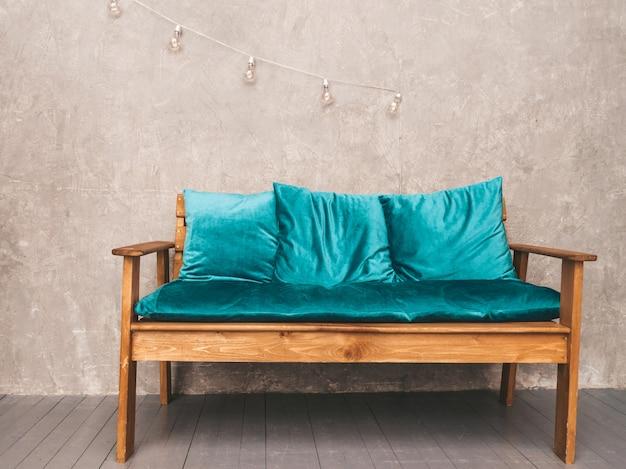 Interior da parede cinza com elegante sofá moderno estofado em azul e madeira, luminárias penduradas Foto gratuita