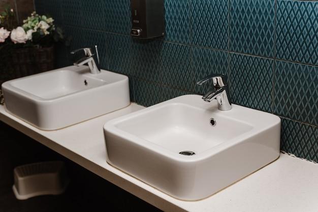 Interior da pia do banheiro público com de lavar as mãos. fechar-se Foto Premium