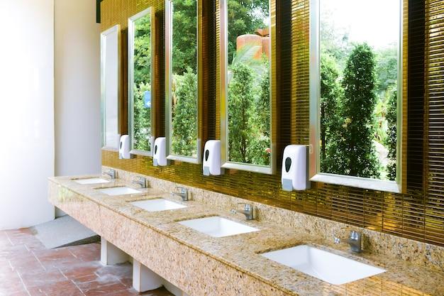 Interior da pia do vaso sanitário público com lava-louças e espelho dourado Foto Premium